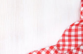 Red picnic cloth on white wooden background.
