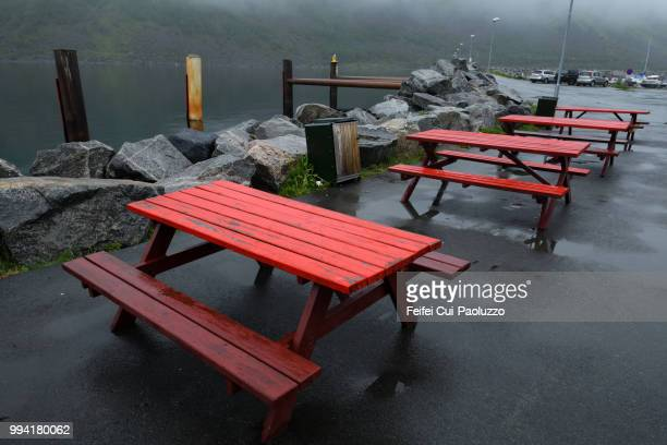 red picnic table at seaside of gryllefjord, norway - picnic table stock pictures, royalty-free photos & images