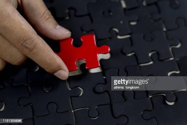 red piece in black puzzle - finale photos et images de collection