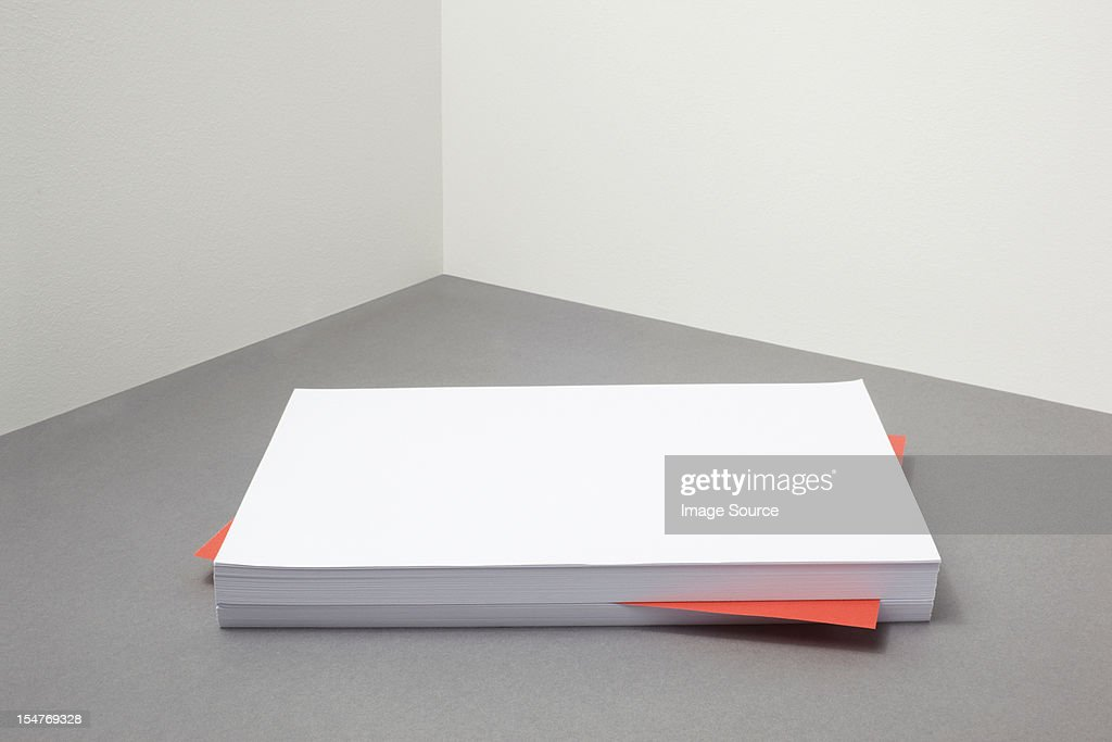 Red piece of paper amongst stack of blank paper : Stock Photo