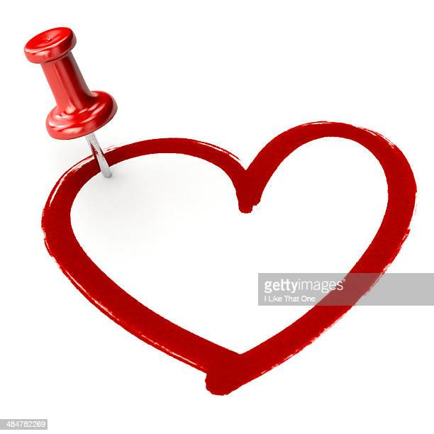 Red pin stuck into a heart drawing