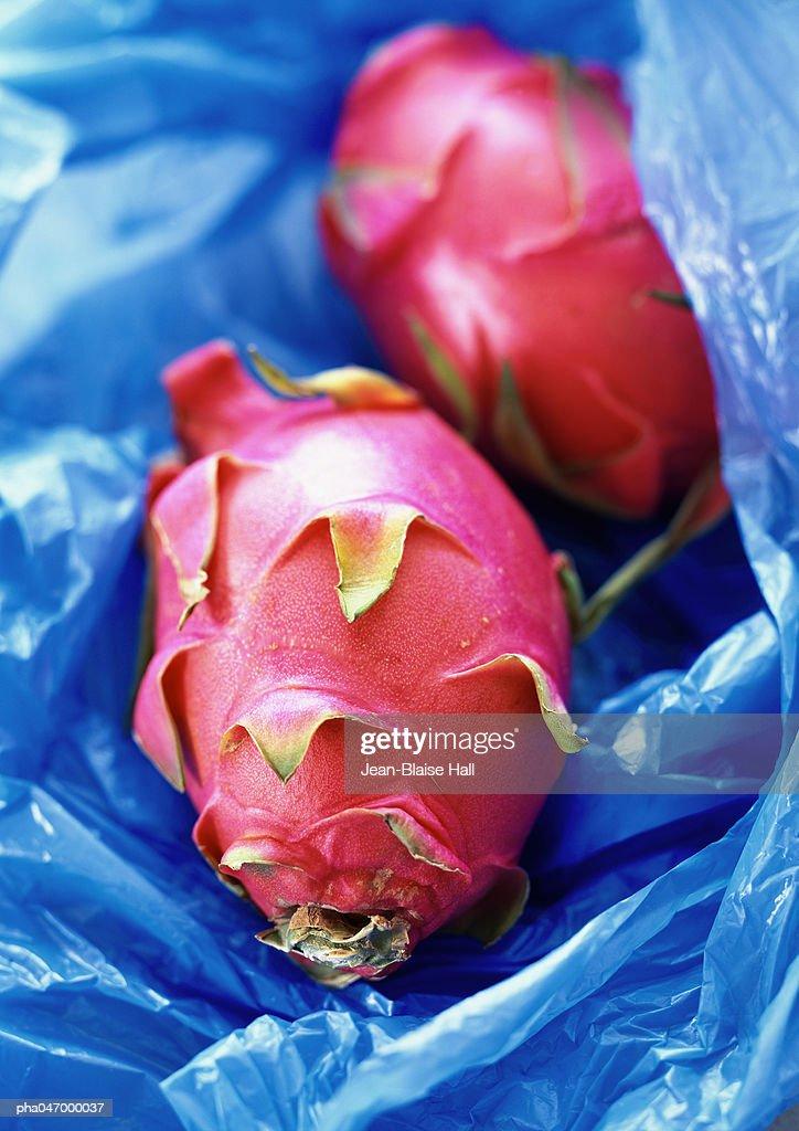 Red pitayas on blue plastic, close-up : Stockfoto
