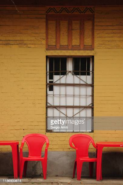 Red plastic chairs and tables by yellow wall