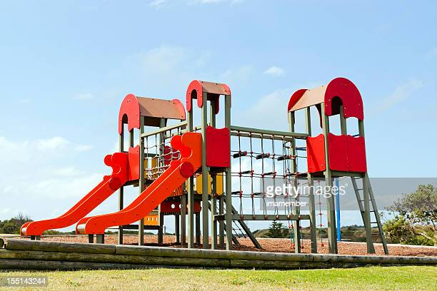 Red playground equipment with slides and ladders against blue sky