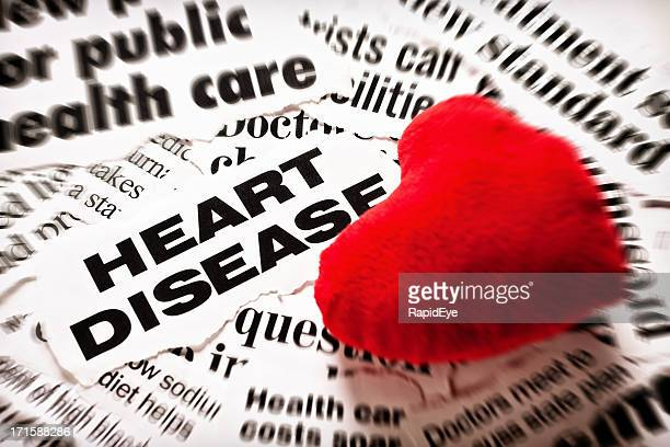 red plush valentine on heart disease headlines - heart disease stock pictures, royalty-free photos & images