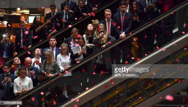 Red poppies fall from above as employees observe a minute's silence in commemoration of Remembrance Day inside Lloyd's of London in the city of...