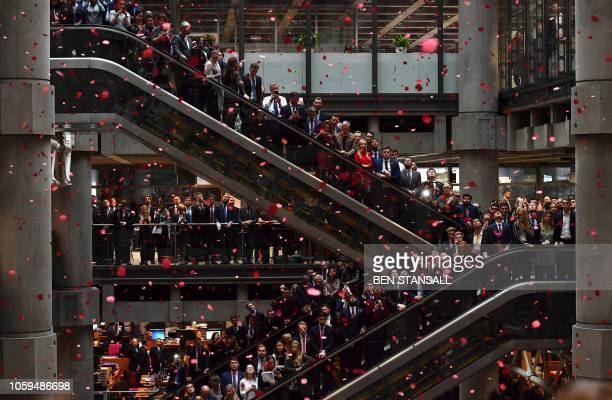 TOPSHOT Red poppies fall from above as employees observe a minute's silence in commemoration of Remembrance Day inside Lloyd's of London in the city...