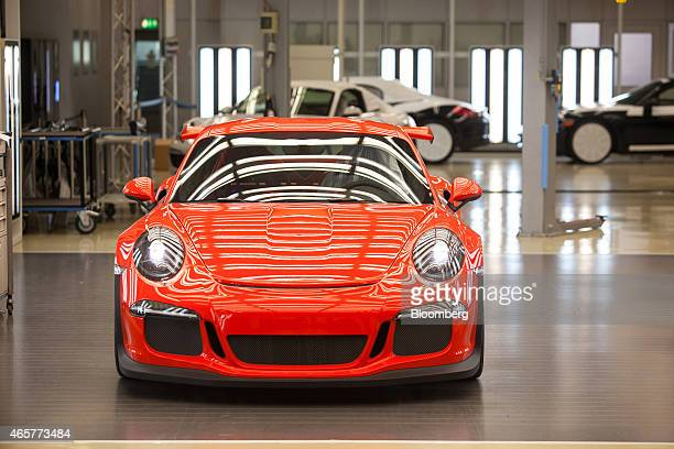 A red Porsche 911 GT3 RS automobile stands illuminated under strip lights ahead of shipping from the Porsche AG factory in Stuttgart Germany on...