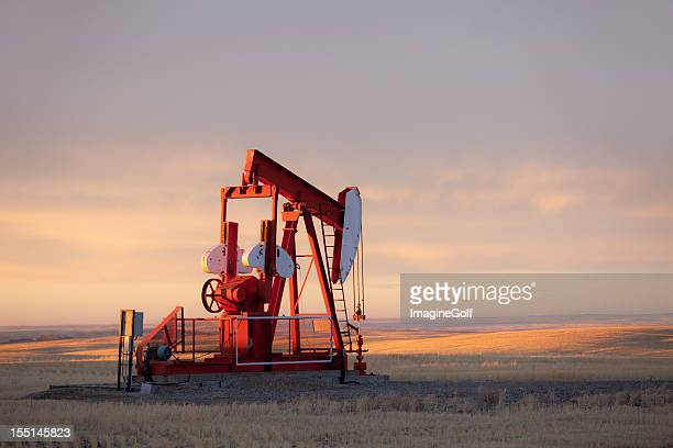 red prairie pumpjack in alberta oil field - alberta stock pictures, royalty-free photos & images