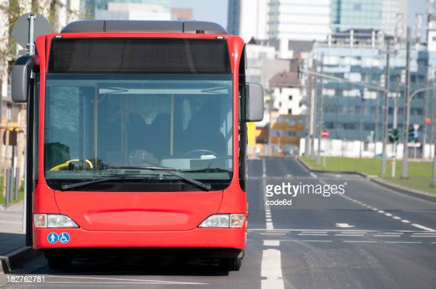 Red public bus at stop, road and copy space