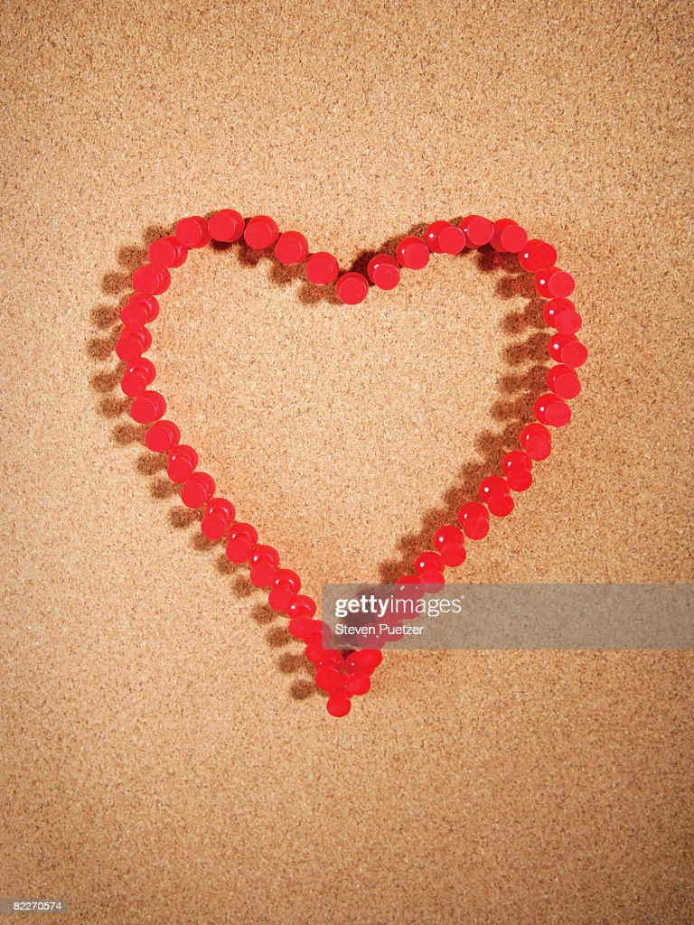 Red push pins on corkboard in the shape of a heart : Stock Photo