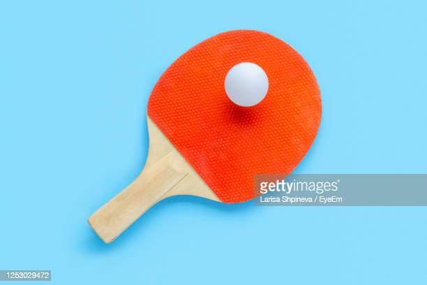 red racket for table tennis with white ball on blue background. ping pong sports equipment - table tennis racket stock pictures, royalty-free photos & images