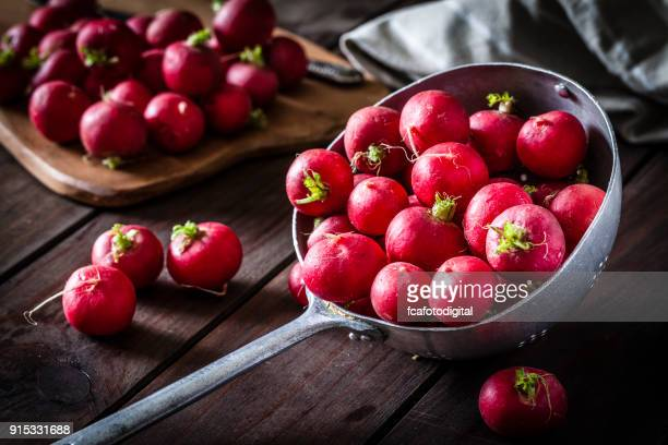 Red radish in an old metal colander