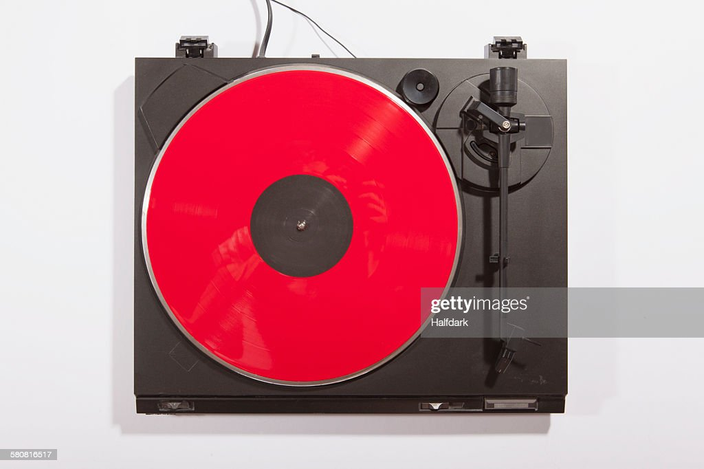 Red record playing on turntable on white background : Stock Photo