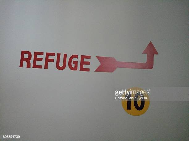 Red Refuge Text With Arrow Symbol On Wall
