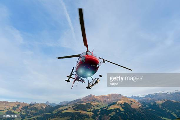 red rescue helicopter landing on mountain