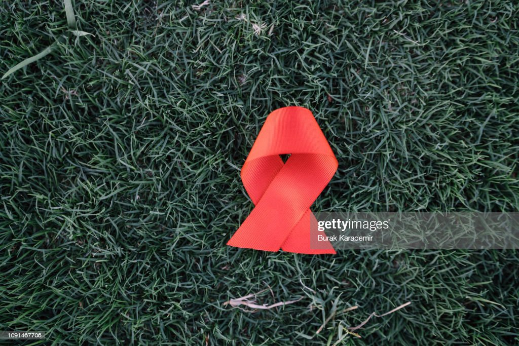Red ribbon awareness on green grass background for World Aids day campaign. : Stock Photo