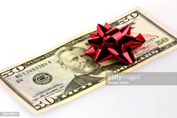Red ribbon decorating a gift of US cash