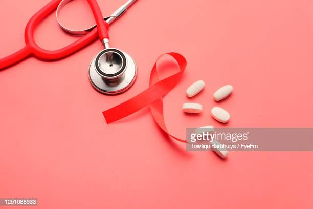 red ribbon hiv, pills and stethoscope on pink background - エイズ ストックフォトと画像