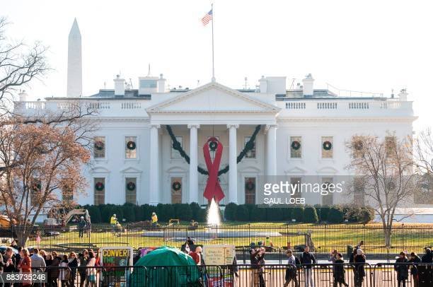 A red ribbon in recognition of World AIDS Day hangs from the North Portico of the White House in Washington DC December 1 2017 / AFP PHOTO / SAUL LOEB