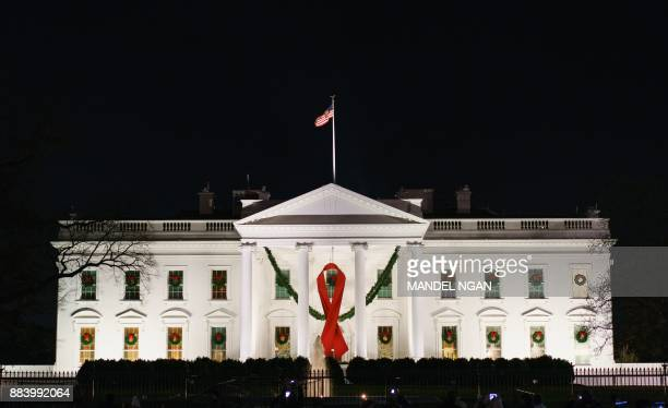 A red ribbon in recognition of World AIDS Day hangs from the North Portico of the White House in Washington DC December 1 2017 / AFP PHOTO / MANDEL...