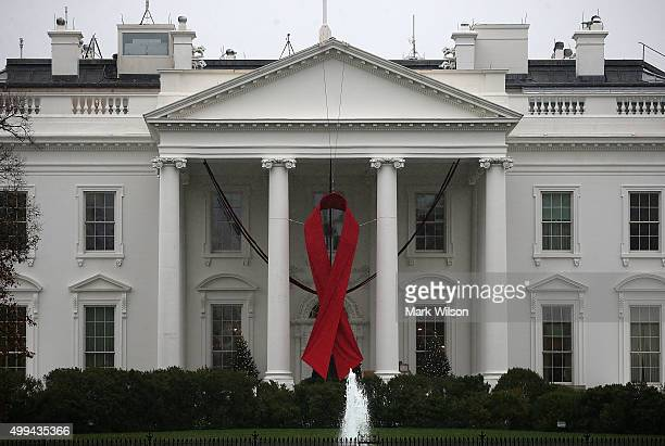A red ribbon is displayed on the North Portico of the White House to recognize World AIDS Day December 1 2015 in Washington DC World AIDS Day has...
