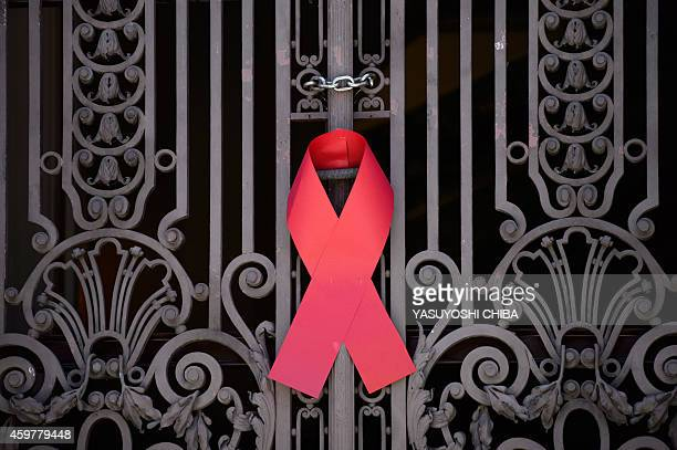 A red ribbon the symbol of HIV/AIDS awareness is put on a gate of the city council chamber during an NGO's campaign on the World AIDS Day in Rio de...