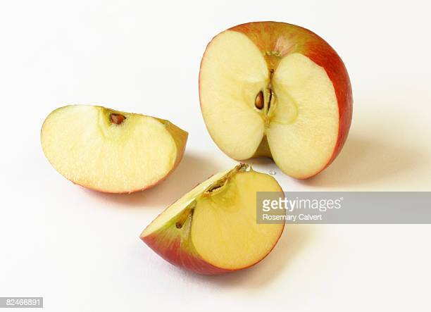 Red, ripe apple cut into one half and two quarters