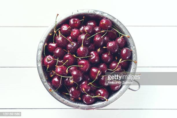 red ripe cherries in drops of water, in an iron plate or colander, on a white wooden table. vegetarian, vegan, raw food. - 西シベリア ストックフォトと画像