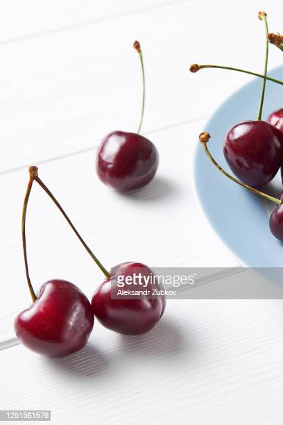 red ripe cherries on a ceramic plate, on a white wooden table. vegetarian, vegan, raw food. - 西シベリア ストックフォトと画像