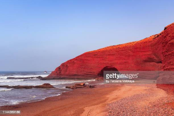 red rock formation with arch on the beach, plage sidi ifni, morocco, africa - agadir stock pictures, royalty-free photos & images