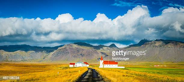 Red roof church and rural village farmhouses cloudscape panorama Iceland