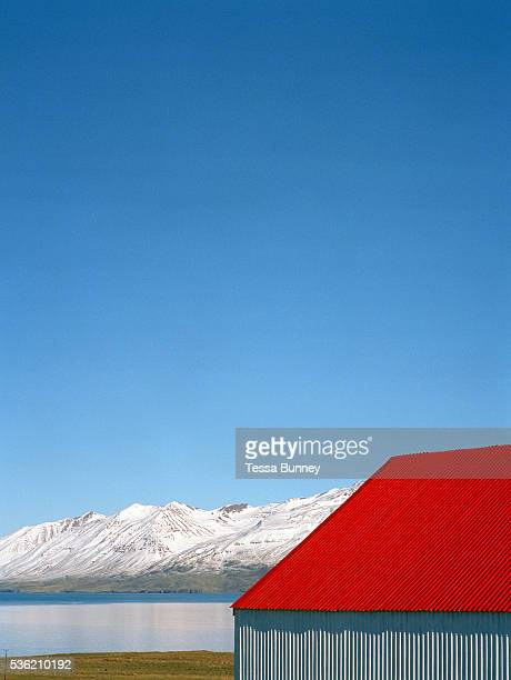 A red roofed farm building overlooking fjord Eyjafjordur and snowy mountains near Dalvik Iceland