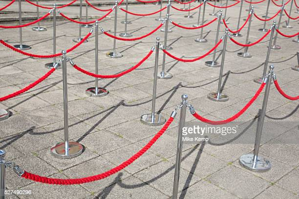 Red rope barriers cordon off an area where a queue will form to help control the flow. London, UK.
