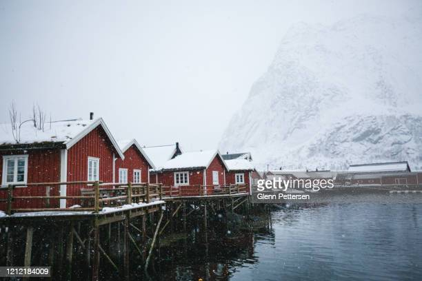 red rorbu against snowy mountain in reine, lofoten. - calm before the storm stock pictures, royalty-free photos & images