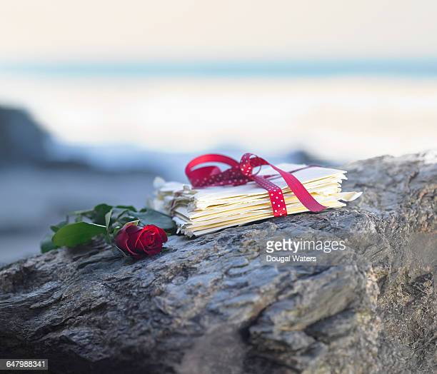 Red rose and bundle of letters on coastal rock.