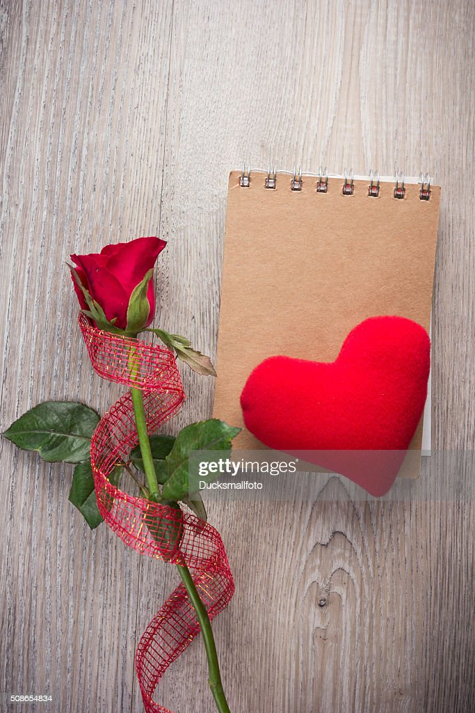 Red rose and note book on old wood background : Stock Photo