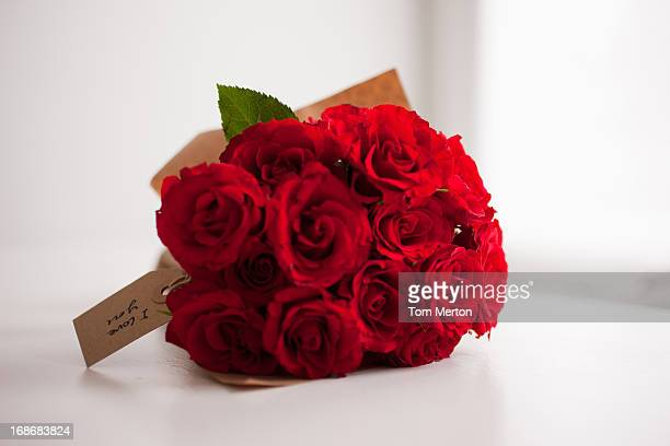 red rose bouquet with gift tag - red roses stock pictures, royalty-free photos & images