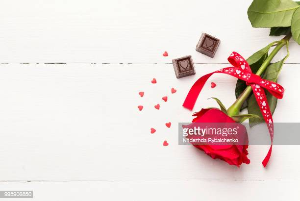 red rose, chocolates on a white wooden background - christmas background stock photos and pictures
