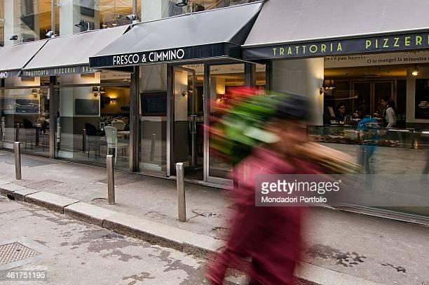 A red rose seller crossing via Ugo Foscolo in front of the pizzeria Fresco e Cimmino Milan Italy 2013