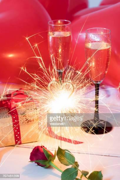 Red rose, sparkler, gift, champagne glasses and balloons