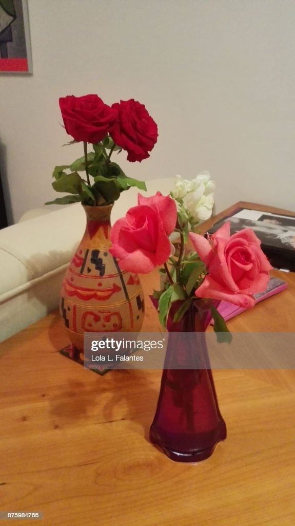 Red roses and pink roses on vases at home : Foto de stock