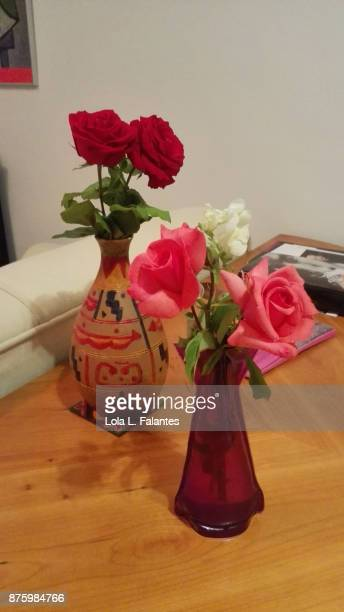 Red roses and pink roses on vases at home