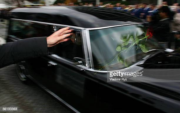 Red roses are thrown onto the hearse containing Aenne Burda from people lining the funeral route after the funeral service on November 10 2005 in...
