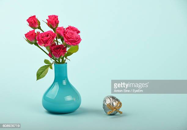Red Roses In Vase With Decoration Against Blue Background
