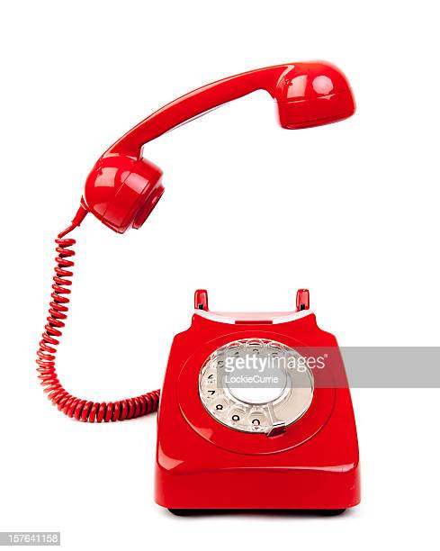 Red rotary dial telephone with cord on white background