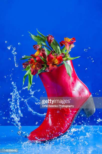 red rubber boot with flowers creating a splash in a puddle. april showers and beauty of spring concept with vibrant colors - bottes photos et images de collection
