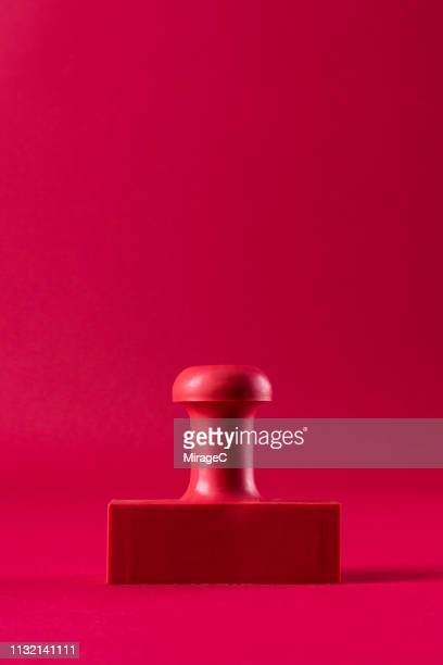 red rubber stamp on red background - timbro foto e immagini stock