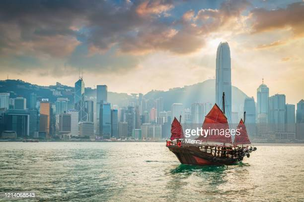 red sail junkboat cruising along hong kong cityscape at sunset - hong kong stock pictures, royalty-free photos & images