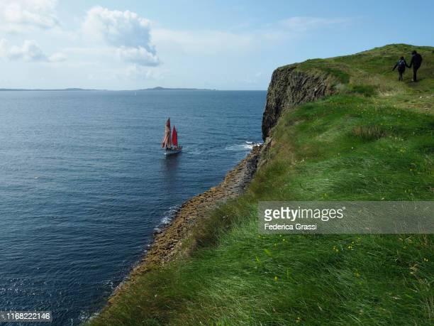 red sailing boat, staffa island, hebrides archipelago, scotland - hebriden inselgruppe stock-fotos und bilder